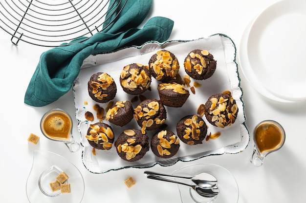 Vegan muffins with banana and almond chips with espresso on tray.