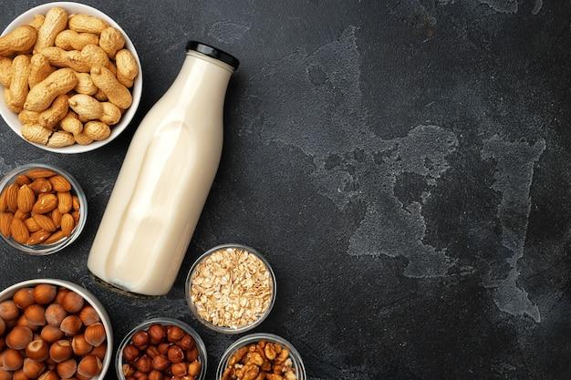 Веганское немолочное ореховое молоко и куча разных орехов на деревянном столе