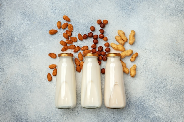 Vegan non dairy nut milk and heaps of different nuts top view on wooden desk