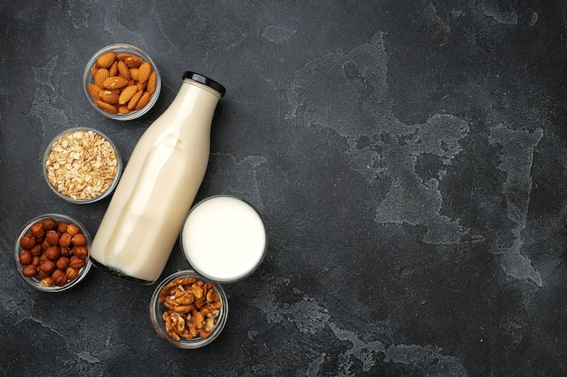 Vegan non dairy nut milk and heaps of different nuts on wooden desk