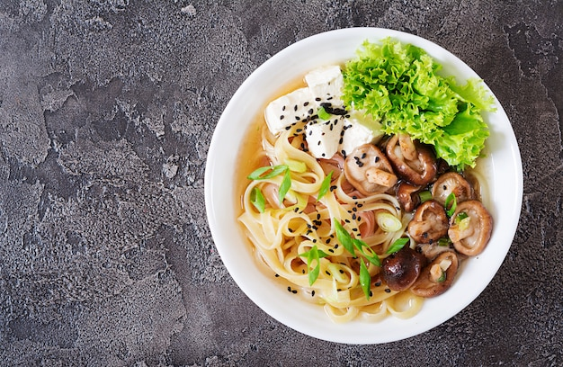 Вегетарианская лапша с сыром тофу, грибами шиитаке и салатом в белой миске. азиатская еда. вид сверху. плоская планировка