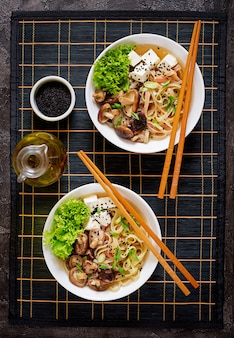 Vegan noodle soup with tofu cheese, shiitake mushrooms and lettuce in white bowl. asian food. top view. flat lay