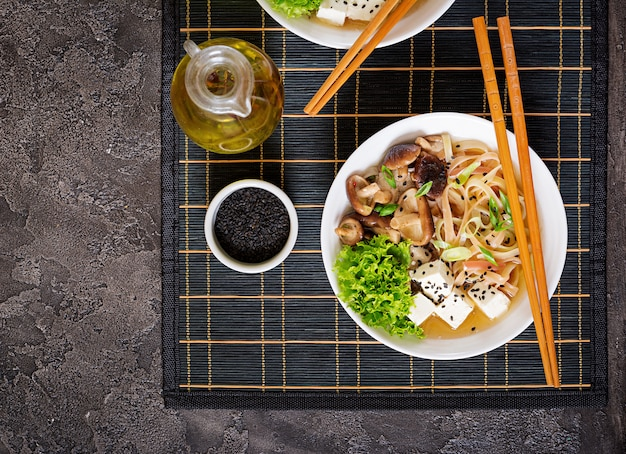 Vegan noodle soup with tofu cheese, shiitake mushrooms and lettuce in white bowl.