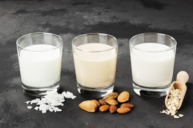 Vegan oat, almond, coconut milk in glass on a dark background. non-dairy milk