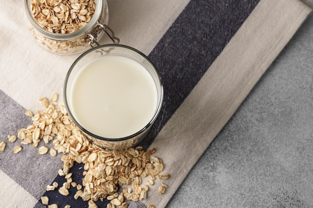 Vegan oat milk with bowl of oat flakes close up