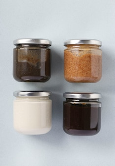 Vegan organic paste of flax seeds, milk thistle, peanuts and coconut in glass jars on light blue table, urbech, vertical format, top view
