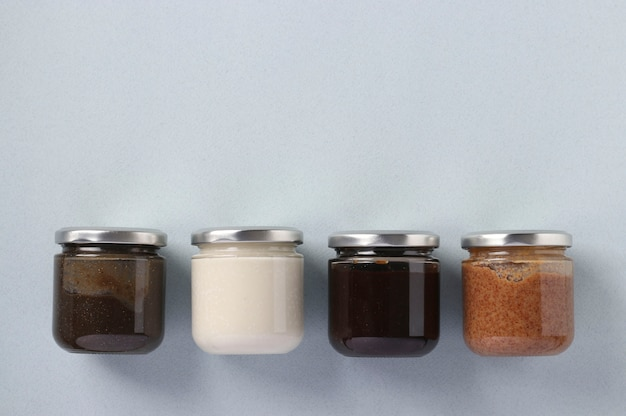 Vegan organic paste of flax seeds, milk thistle, peanuts and coconut in glass jars on light blue