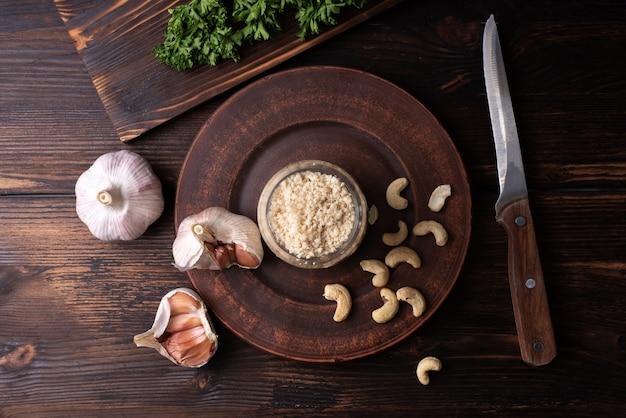파슬리와 마늘 정향을 나무 배경에 넣은 채식주의 파마산 치즈 캐슈넛, 채식주의 음식이 닫힙니다.