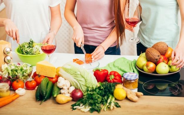 비건 파티. 친구 요리. 부엌에서 티셔츠에 여성. 과일 및 야채 구색. 레드 와인 잔.