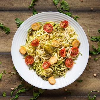 Vegan pasta in plate on wooden background