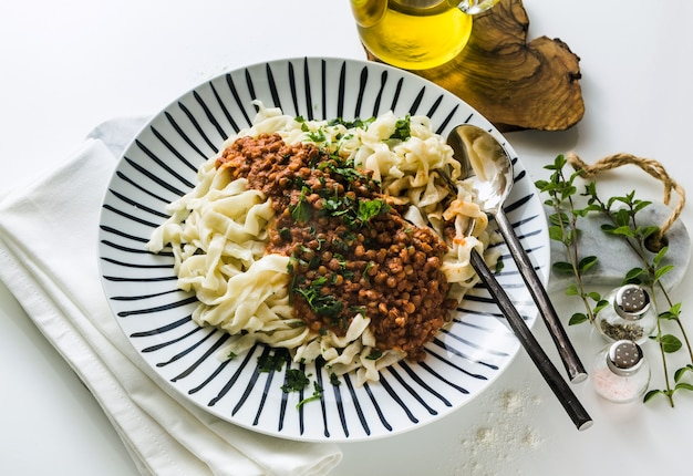 Vegan pasta with lentil and tomato sauce in a plate on the table