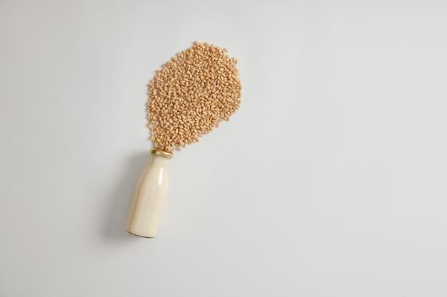 비타민과 영양소가 가득한 비건 채식 음료입니다. 흰색 배경 위에 유리 병에 신선한 두유. 클래식 우유의 대안. 건강한 채식 음료, 좋은 칼슘 공급원