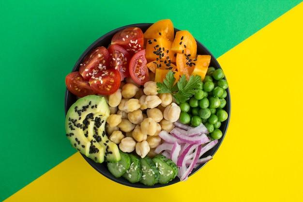 中央の黒いボウルにひよこ豆と野菜が入ったビーガンポークボウル。上面図。クローズアップ。