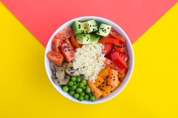 二色のテーブルの中央にある白いボウルにクスクスと野菜が入ったビーガンポークボウル。上面図。スペースをコピーします。閉じる。