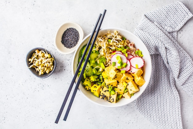 Vegan poke bowl with pickled tofu, vegetables and rice in a white bowl, top view.