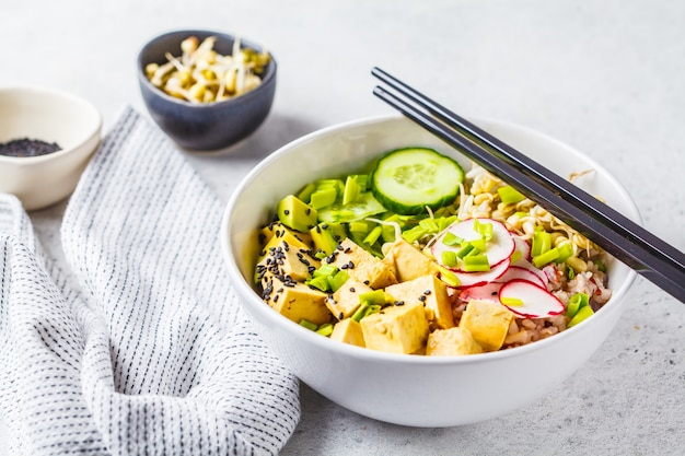 Vegan poke bowl with pickled tofu, vegetables and rice in a white bowl.