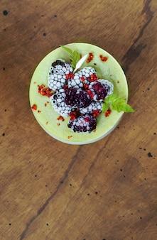 Vegan raw cheesecake with blueberry, cherry, matcha tea, orange,  cashew cream, coconut butter and coconut milk