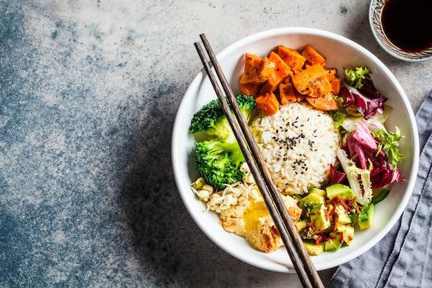 비건 밥과 야채 샐러드. 쌀, 후 머스, 아보카도, 브로콜리 및 고구마로 설정된 macrobiotic
