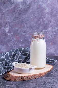 ガラスの瓶にビーガンライスミルクと灰色のナプキンで灰色の背景に木製のスタンドに白い皿にご飯