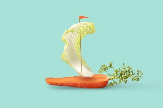 Веганский парусник из органических овощей на пастельно-бирюзовом фоне.