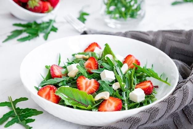 ほうれん草のフェタチーズとカシューナッツを添えたイチゴのビーガンサラダ健康的な栄養とビタミン
