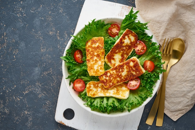 Vegan salad with fried halloumi and tomatoes, dark , top view copy space