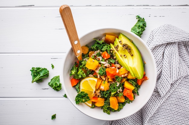 Vegan salad with rice, kale, baked pumpkin, carrots and avocado in white bowl