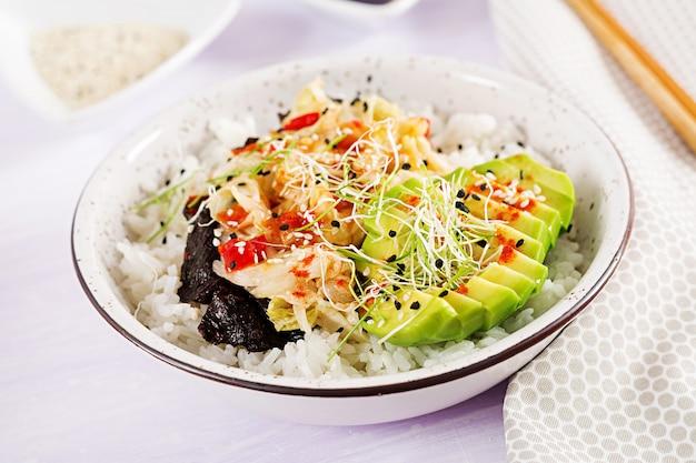 Веганский салат с рисом, маринованной капустой кимчи, авокадо, нори и кунжутом в миске.