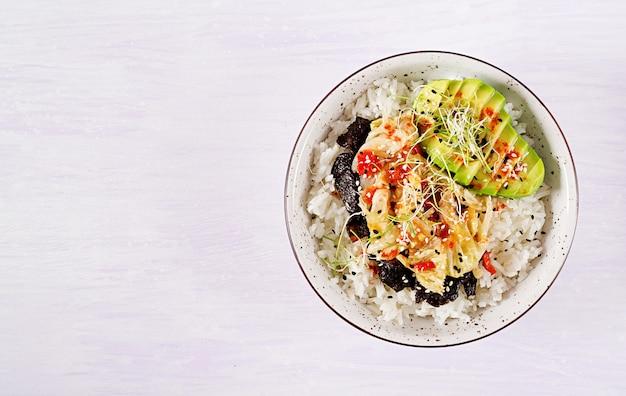 밥에 절인 김치 양배추, 아보카도, 김, 참깨를 넣은 비건 샐러드.