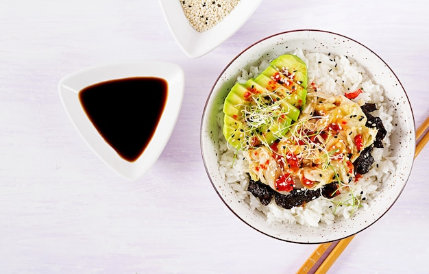 Vegan salad  with rice, pickled kimchi cabbage, avocado,  nori and sesame on bowl