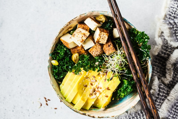 Vegan salad with smoked tofu, kale, avocado and sprouts in bowl,