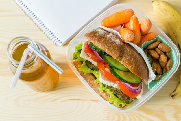 Vegan sandwich in lunch box with carrots and nuts