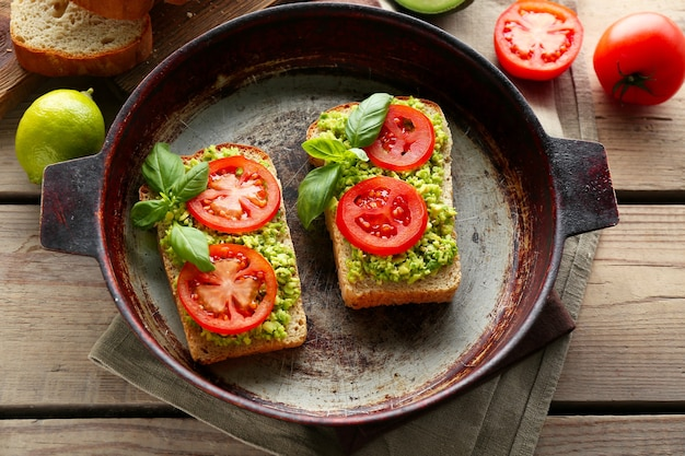 Vegan sandwich with avocado and vegetables on pan, on wooden