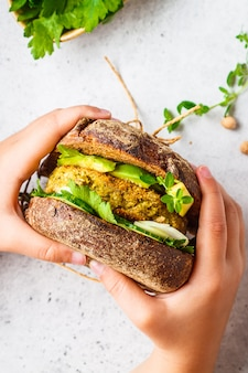 Vegan sandwich with chickpea patty, avocado, cucumber and greens in rye bread