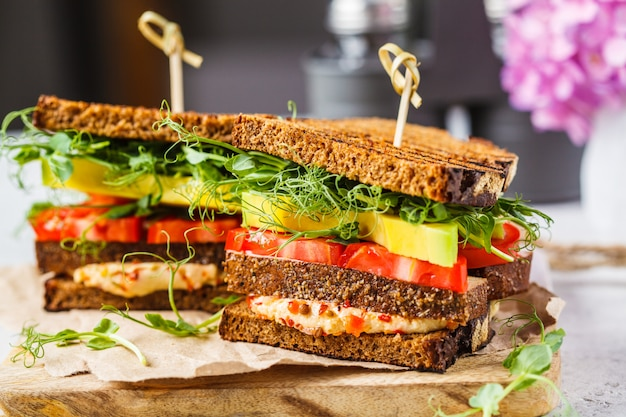 Vegan sandwich with tofu, hummus, avocado, tomato and sprouts.