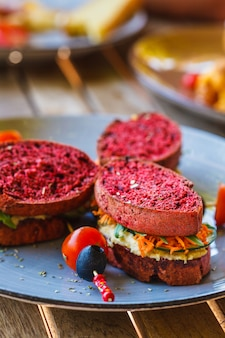 Vegan sandwiches for breakfast with beetroot bread, hummus and vegetables