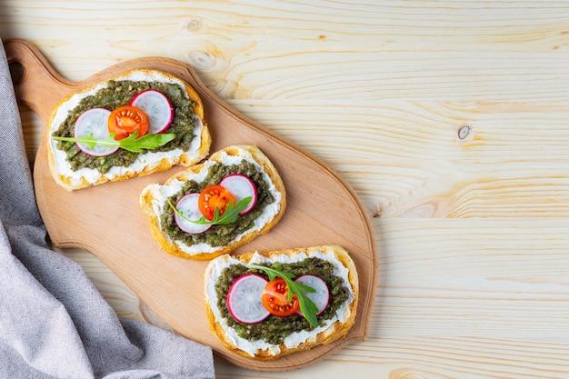 도마에 아보카도 크림을 곁들인 비건 샌드위치.