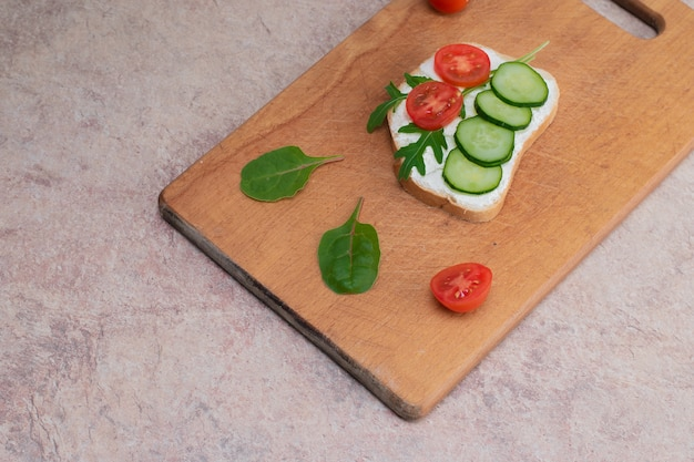 Веганские бутерброды с домашним творожным кремом с зеленью, с редисом, огурцами и помидорами. на деревянной разделочной доске.
