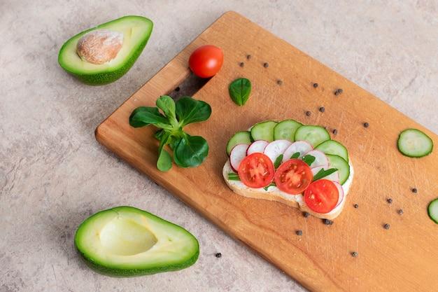 Веганские бутерброды с домашним творожным кремом с зеленью, с редисом, огурцами, авокадо и помидорами. на деревянной разделочной доске.