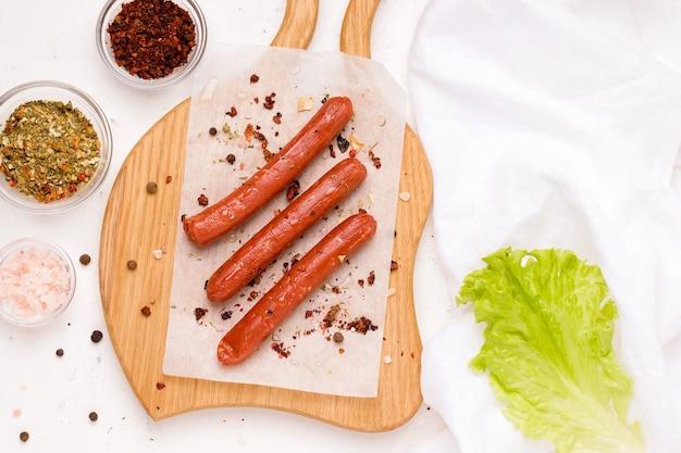 Веганские сосиски со специями и помидорами на белой тарелке. скопируйте пространство.