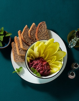 Vegan snack of spread of roasted beets and pistachios and leaves of belgian endive with whole grain bread on the table