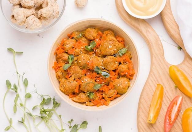 Веганское соевое мясное блюдо с овощами на белой тарелке