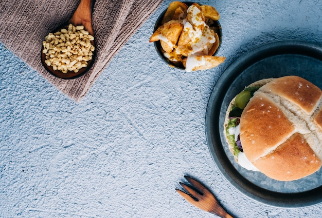 Vegan soy protein hamburger with french fries with spices in metal bowl. copy space. top view