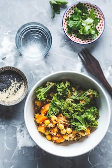 Vegan stew with chickpeas, sweet potato and kale in white bowl, top view.