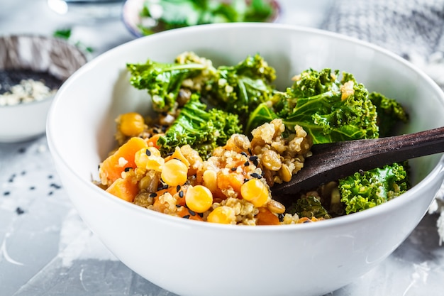 Vegan stew with chickpeas, sweet potato and kale in white bowl.