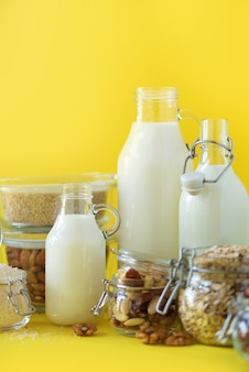 Vegan substitute dairy milk. glass bottles with non-dairy milk and ingredients over yellow background with copy space.