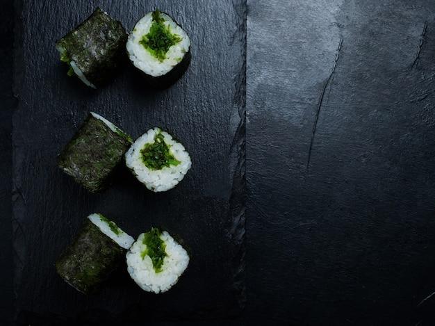 暗い背景にビーガン寿司が転がる
