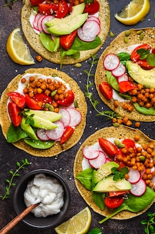Vegan tacos with baked chickpeas, avocado, sauce and vegetables , top view.