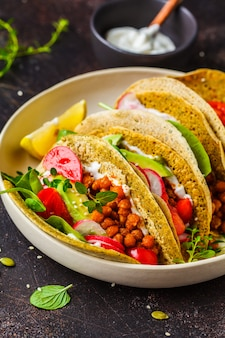 Vegan tacos with baked chickpeas, avocado, sauce and vegetables .