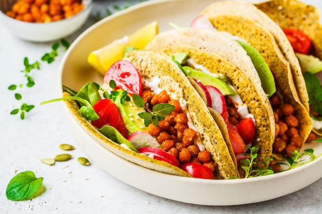 Vegan tacos with baked chickpeas, avocado, sauce and vegetables